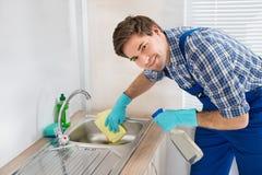 Lavandino di pulizia del lavoratore nella stanza della cucina immagini stock