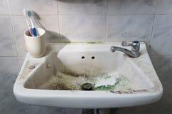 Lavandino sporco con lo spazzolino da denti e rubinetto in bagno sporco fotografie stock libere da diritti