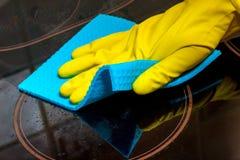 lavando la cucina elettrica con una superficie vetro-ceramica - una mano gloved con uno straccio immagini stock libere da diritti