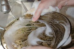 Lavando o prato com suas mãos imagem de stock