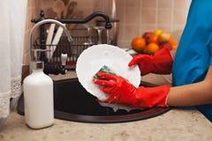 Lavando os pratos após uma refeição - a criança entrega a esfrega de uma placa fotografia de stock royalty free