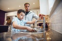 Lavando os pratos com paizinho imagem de stock royalty free