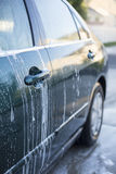 Lavando um carro na lavagem de carros Imagens de Stock Royalty Free