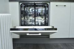 Lavaplatos blanco moderno con una puerta abierta fotografía de archivo