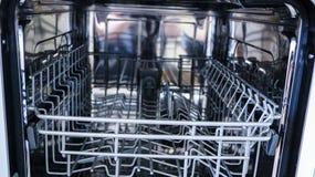 Lavaplatos con la puerta abierta estantes internos del lavaplatos para la distribución de platos y de la cesta para los cubiertos fotos de archivo libres de regalías