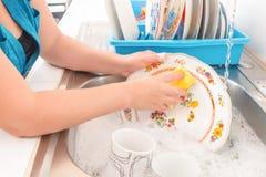 Lavar los platos en el fregadero de cocina Fotografía de archivo libre de regalías