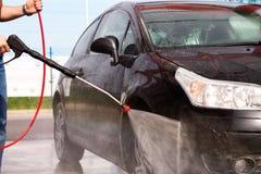 Lavar un coche con la lavadora de la presión Foto de archivo