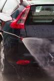 Lavar un coche con la lavadora de la presión Imagenes de archivo