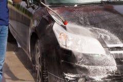 Lavar un coche con la lavadora de la presión Fotografía de archivo