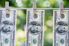Lavare e di soldi Dollari americani di riciclaggio di denaro andati in giro per asciugarsi 100 banconote in dollari che appendono Fotografia Stock