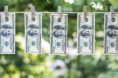 Lavare e di soldi Dollari americani di riciclaggio di denaro andati in giro per asciugarsi 100 banconote in dollari che appendono Immagini Stock