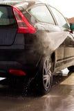 Lavare un'automobile con la rondella di pressione Fotografia Stock