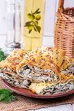 Lavash roll with cottage cheese and greens on a plate stock photos