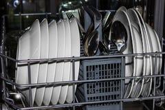 Lavastoviglie della cucina con i piatti, le forchette ed i cucchiai Fotografia Stock