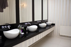 Lavatory. A lavatory with washbasins in black and white design Stock Photos