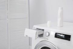 Lavatrice con la bottiglia del detersivo nel giorno della lavanderia fotografie stock