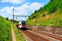 Lavaux, Switzerland - August 30, 2016: Running train near Lavaux Vineyard Terraces hiking trail, Lavaux-Oron district, Switzerland. Lavaux, Switzerland - August royalty free stock photography