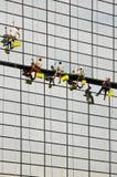 Lavavetri che appendono sulle corde e sulle finestre di pulizia di un edificio per uffici immagini stock