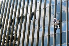 Lavavetri dello scalatore che puliscono parete di vetro esteriore di una costruzione fotografia stock