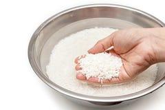 Lave el arroz con agua en el cuenco inoxidable foto de archivo libre de regalías