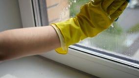 Lave a janela suja com um raspador em uma luva de borracha amarela Movimento lento HD, 1920x1080 video estoque