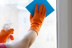 Lave la ventana con el agente de limpieza Imagen de archivo libre de regalías