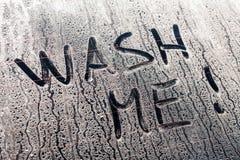 Lave-me palavras em uma janela de carro suja Fotografia de Stock