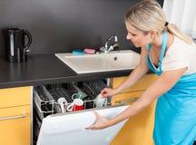 Lave-vaisselle d'ouverture de femme images stock