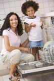 Lave-vaisselle de charge de mère et de descendant photo stock