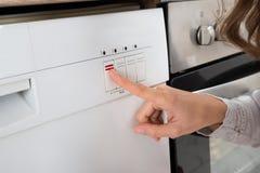 Lave-vaisselle de Person Hands On Button Of image libre de droits