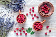 Laveder composition with raspberry in pottery cup rustic background top view Stock Image