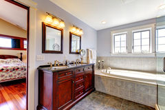 Lavendar bathroom with tub and wood cabinet Stock Photography