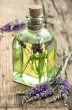 Lavendelöl mit frischen Blumen auf hölzernem Hintergrund stockbilder