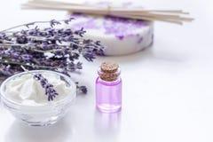 Lavendelörter i kroppomsorgskönhetsmedel med olja på vit tabellbakgrund Fotografering för Bildbyråer