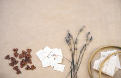Lavendel, houten knopen, eigengemaakte enveloppen, oude houten hoepel en linten met boord op ambachtdocument stock foto's
