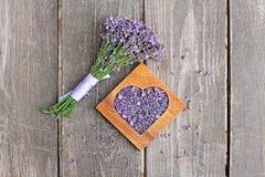 Lavendel i trähjärta-formad ask och grupp av lavendel blommar Arkivfoton