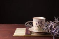 Lavendel met kop thee en cake op de zwarte achtergrond Royalty-vrije Stock Foto's