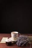 Lavendel met kop thee en cake op de zwarte achtergrond Stock Afbeelding