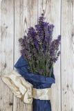 Lavendel som slås in i papper med det siden- bandet på träbakgrund Arkivbild