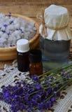 Lavendelbadekurort, Bündel Lavendelblumen, ätherisches Öl und Salz auf einem rustikalen hölzernen Hintergrund Lizenzfreie Stockbilder