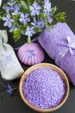 Lavendelbadsalt med blommor, tvål, påsen och handduken Fotografering för Bildbyråer