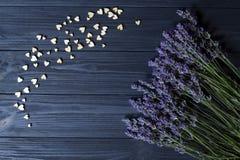 Lavendelbloemen en houten liefdeharten op een donkerblauwe houten lijst royalty-vrije stock fotografie