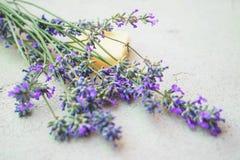 Lavendelbloemen en natuurlijke zeep voor bodycare op concrete achtergrond stock fotografie