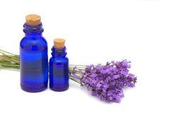 Lavendelbloemen en uitstekende fles Stock Afbeelding