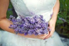 Lavendelblumenstrauß in den Händen der Braut stockfotos