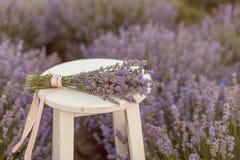Lavendelblumenstrauß in einer Holzbank im levender archivierte Sonnenuntergang Lizenzfreie Stockfotos
