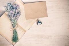 Lavendelbukett som läggas över en gammal bok, en silverhjärta och ett kuvert för kraft papper på en vit träbakgrund tappning för  Royaltyfri Bild