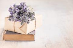 Lavendelbukett som läggas över en gammal bok på en vit träbakgrund tappning för stil för illustrationlilja röd Arkivfoton