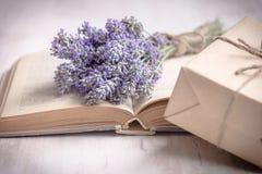 Lavendelbukett som läggas över en gammal bok och en slågen in gåvaask på en vit träbakgrund tappning för stil för illustrationlil Arkivbilder