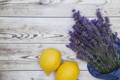 Lavendelbukett som slås in i papper med citroner på träbakgrund Arkivbild